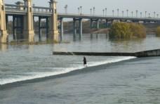 河中撒网的人图片